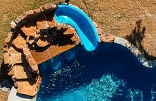 blue-slide-on-rock-waterfall-on-freeform-pool