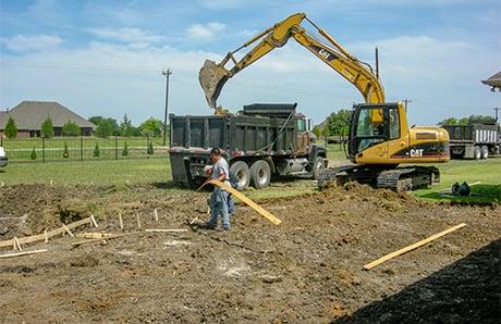 excavator-shoveling-soil-into-dump-truck