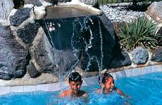 kids-in-pool-below-waterfall