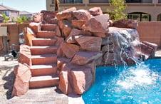 masonry-steps-to slide-on-rock-waterfall-on-pool
