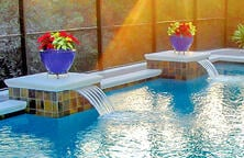 potted-flowers-atop-pedestals-on-inground-pool