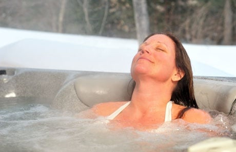 woman relaxing in hot tub during winter